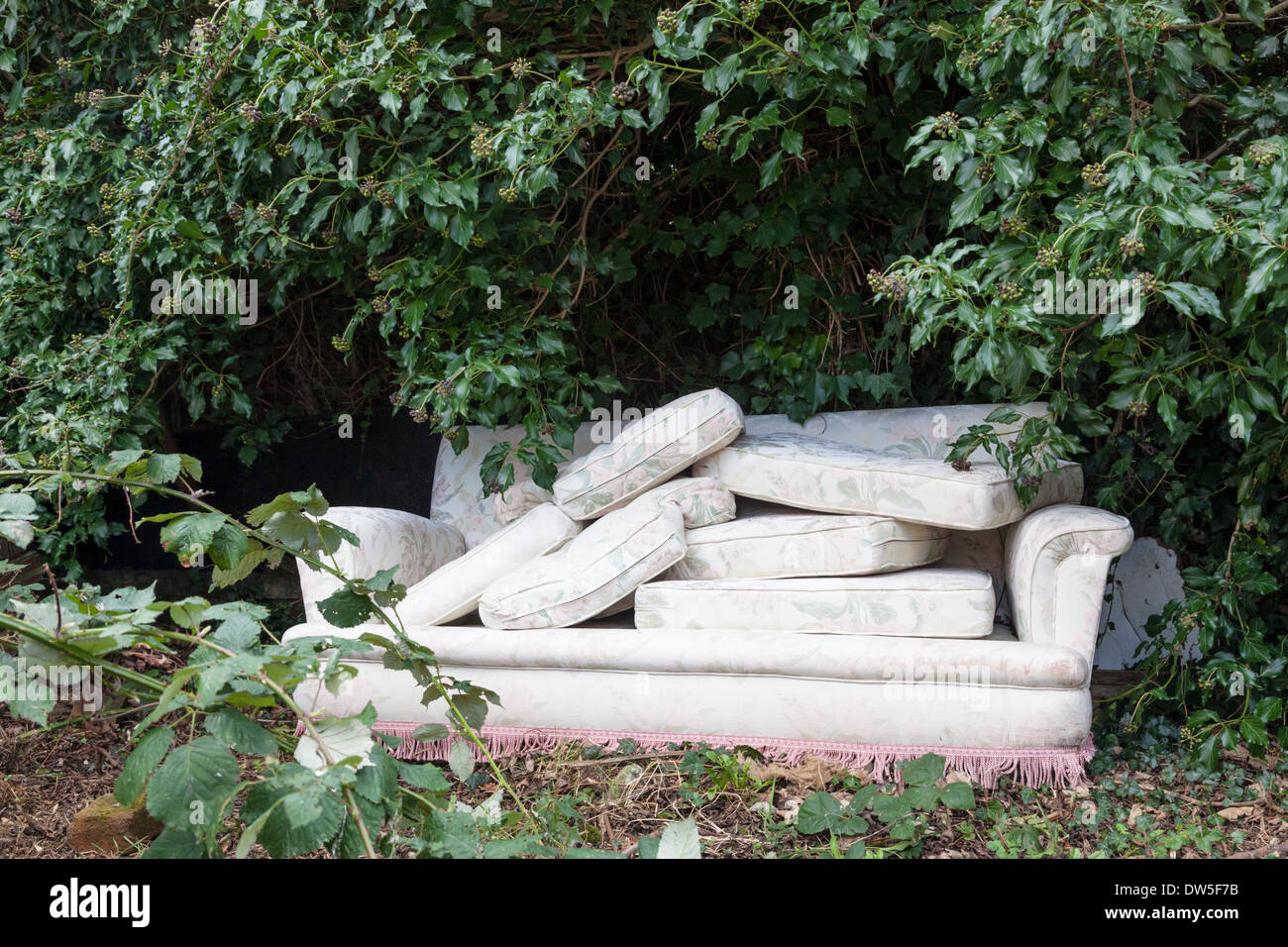 Fly tipping in the UK. Illegal dumping of furniture underneath a tree, Nottinghamshire, England, UK Stock Photo