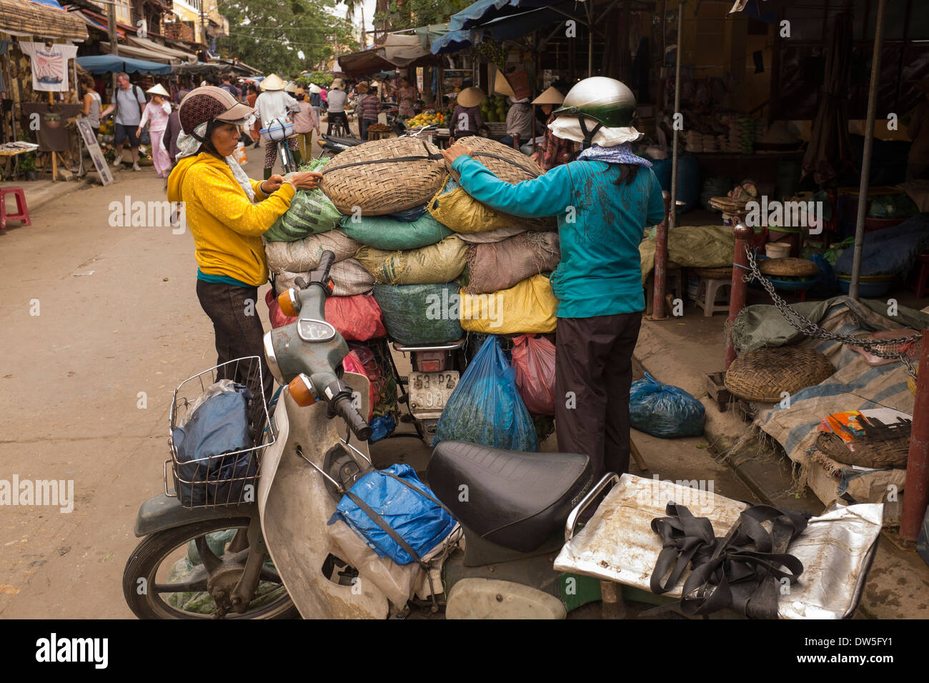 Ladies loading vegetable sacks on to the back of motorbike in the market Hoi An - Stock Image