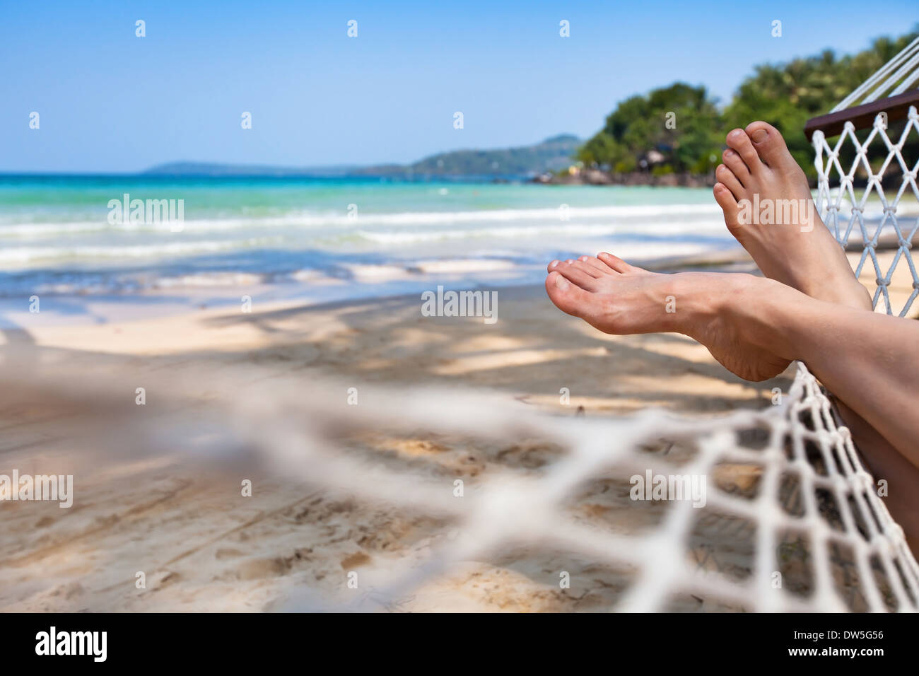 woman feet in hammock on the beach - Stock Image