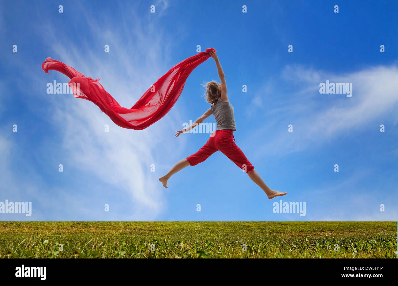 happy girl jumping with red fabric - Stock Image
