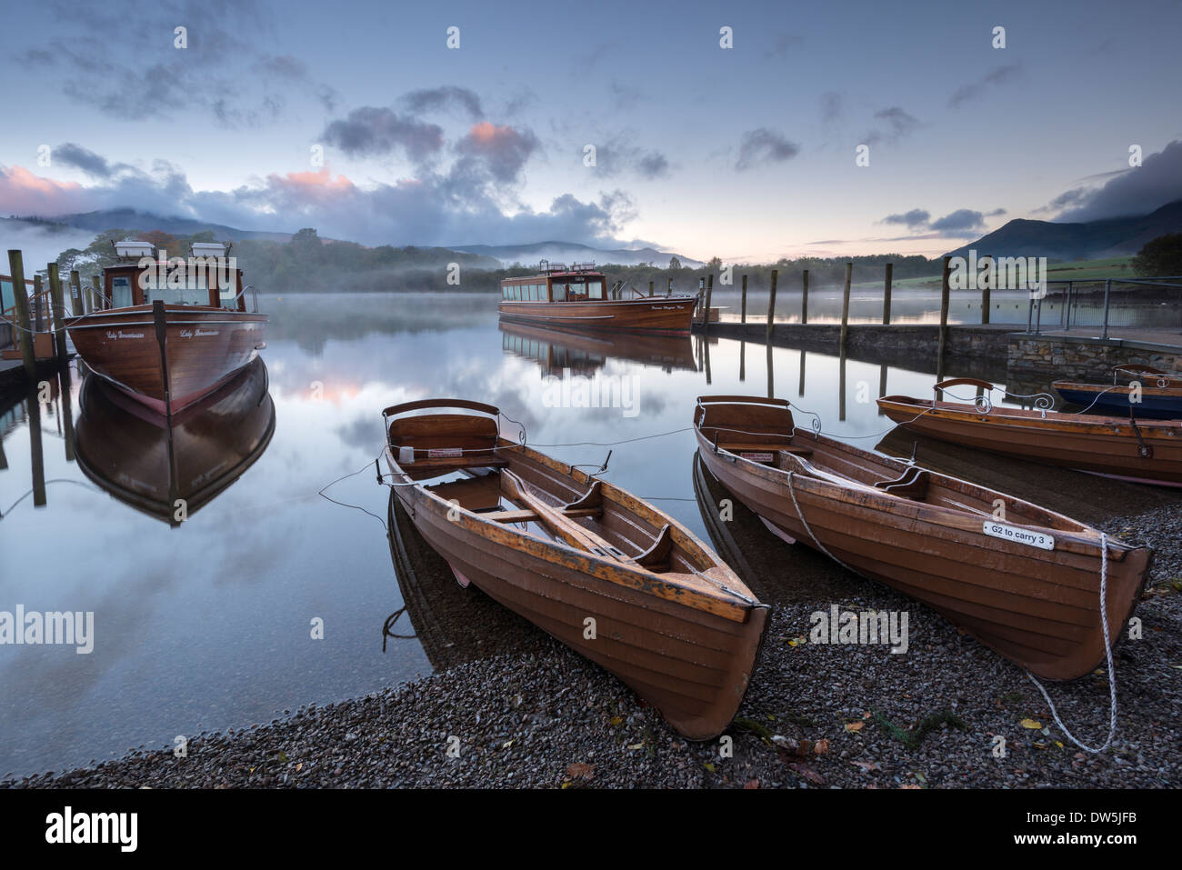 Boats moored on Derwent Water at dawn, Keswick, Lake District, Cumbria, England. Autumn (October) 2012. - Stock Image