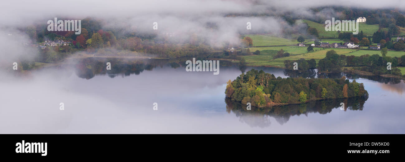 Grasmere lake and village appears through swirling morning mist, Lake District, Cumbria, England. Autumn (October) 2013. - Stock Image
