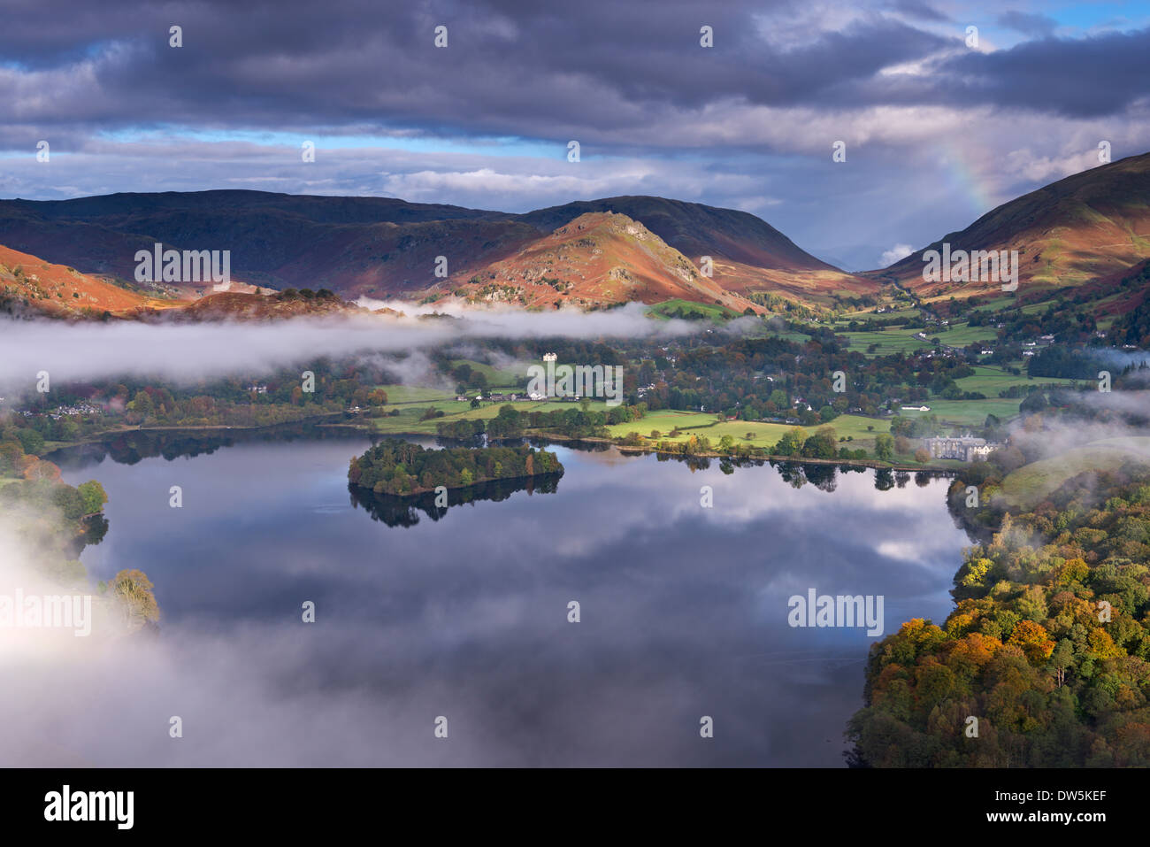 Mist burns off Lake Grasmere in the early morning, Lake District, Cumbria, England. Autumn (October) 2012. - Stock Image