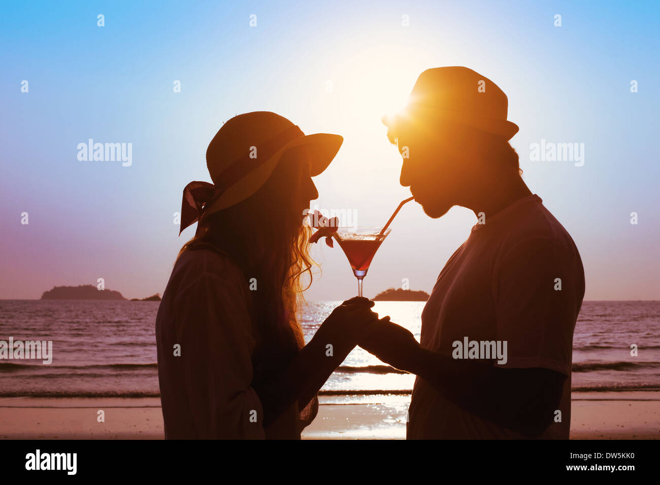 share the pleasure, couple drinking cocktail on the beach - Stock Image