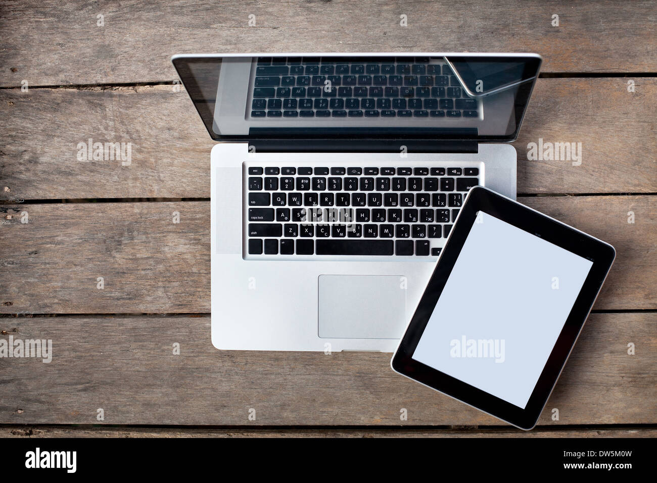 laptop and tablet on old wooden desk - Stock Image