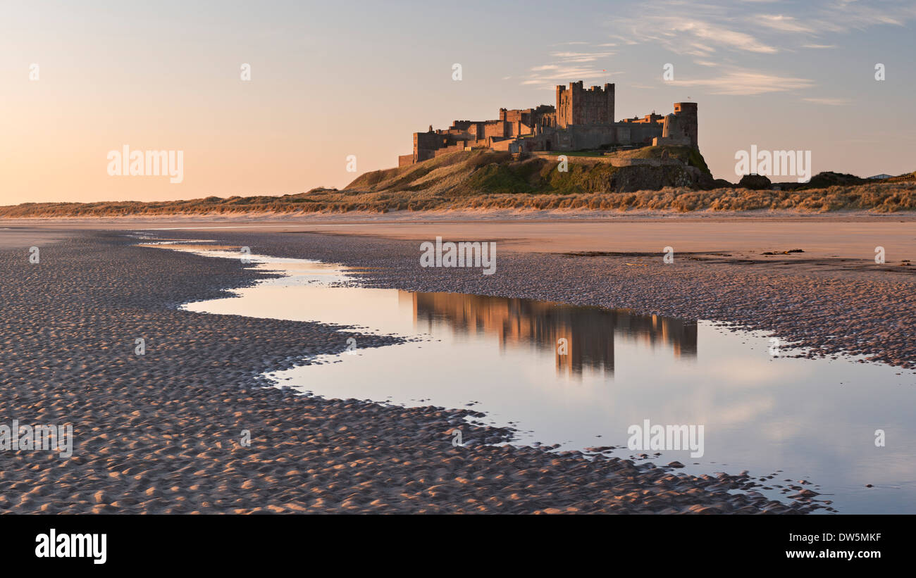 Bamburgh Castle and reflection in Bamburgh Beach tidal pools, Northumberland, England. Spring (April) 2013. - Stock Image