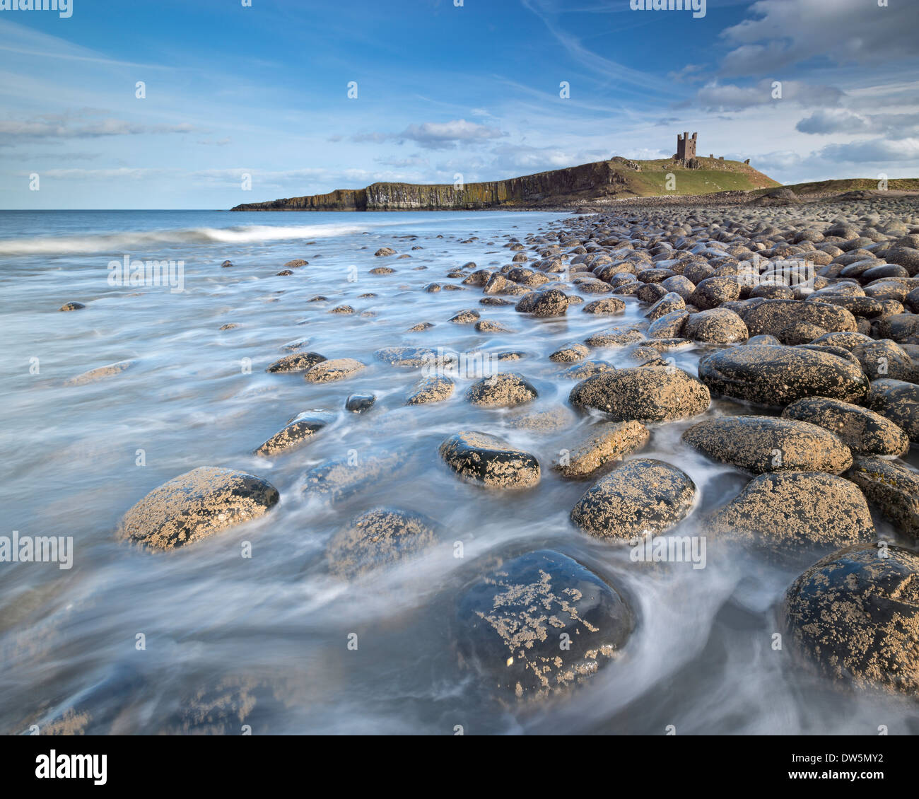 The ruins of Dunstanburgh Castle overlooking the boulder strewn shores of Embleton Bay, Northumberland, England. Stock Photo