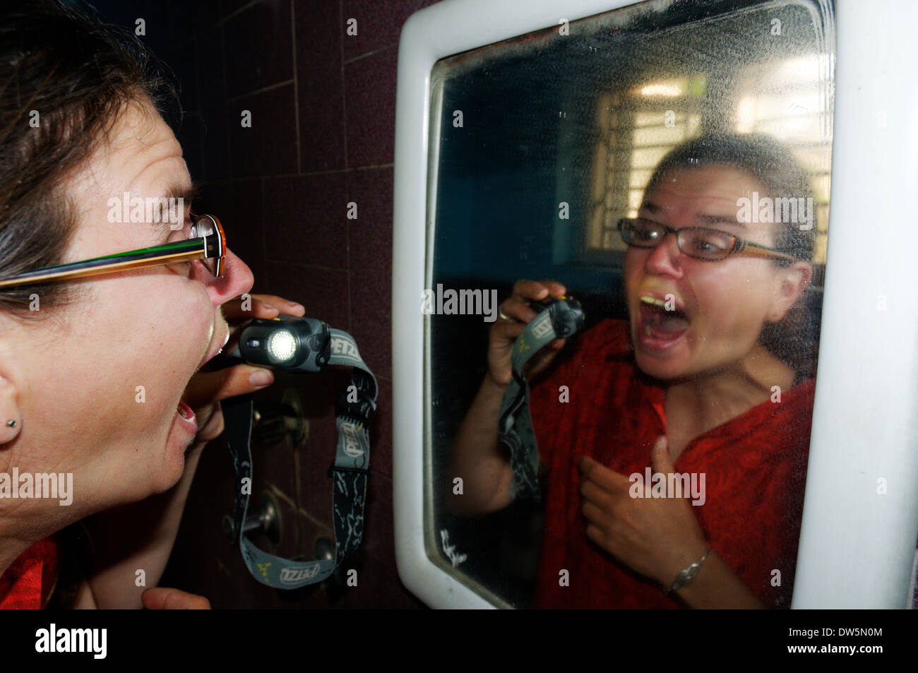 A woman checking her sore throat with a head torch in a mirror - Stock Image