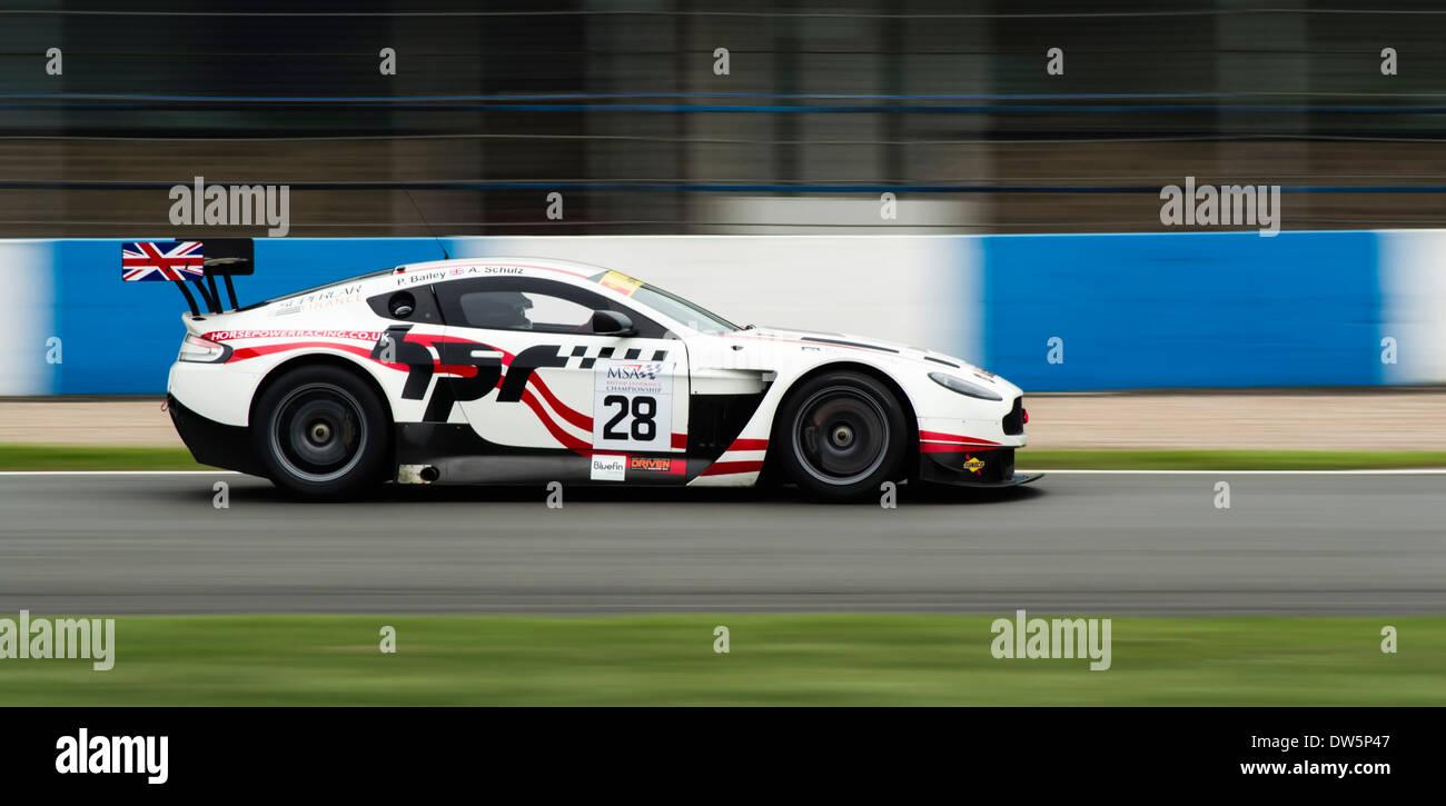 Horsepower Racing and Aston Martin Racing's GT3 car driving full speed around Donington Park Circuit. - Stock Image