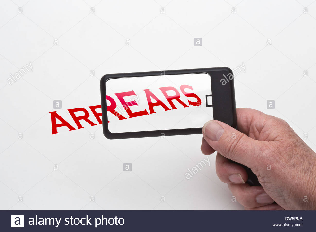 Mans hand holding a magnifying glass showing the word arrears being magnified. - Stock Image