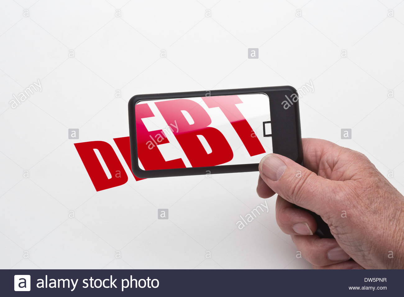 Mans hand holding a magnifying glass showing the word debt being magnified. - Stock Image