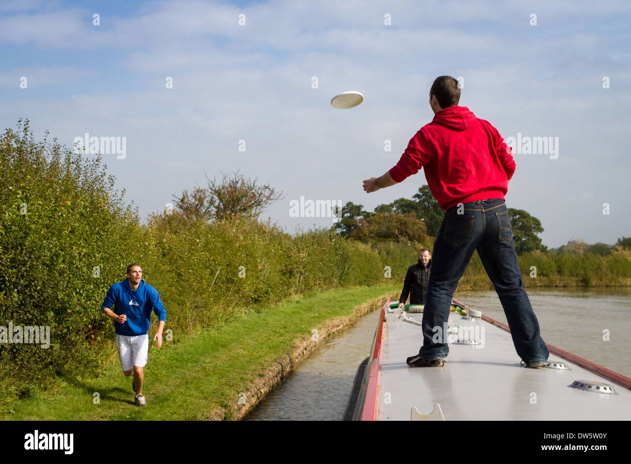 A group of men playing Frisbee on a narrowboat - Stock Image