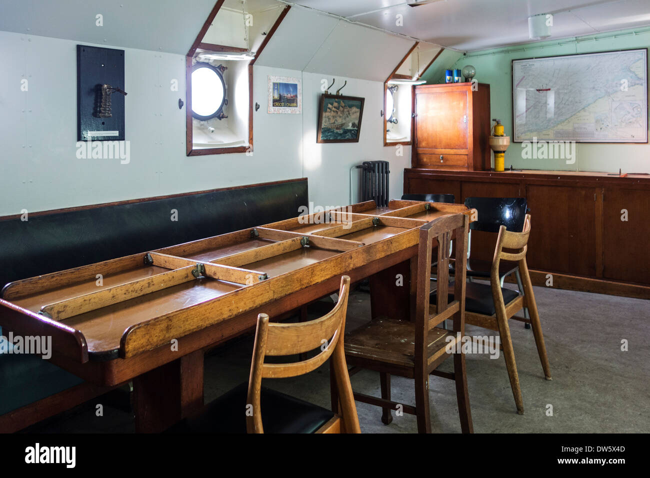 Special dinner table divided in compartments with wooden boards to prevent food from gliding in mess room on board of ship - Stock Image
