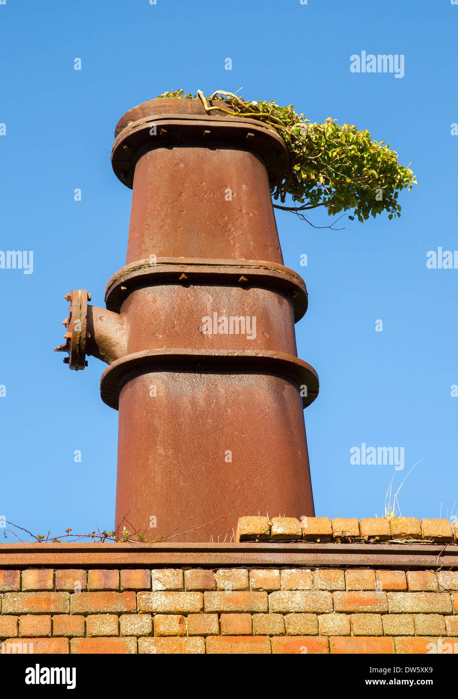 Disused oil extraction retort at Kilve Somerset with ivy on the chimney remeniscent of smoke - Stock Image