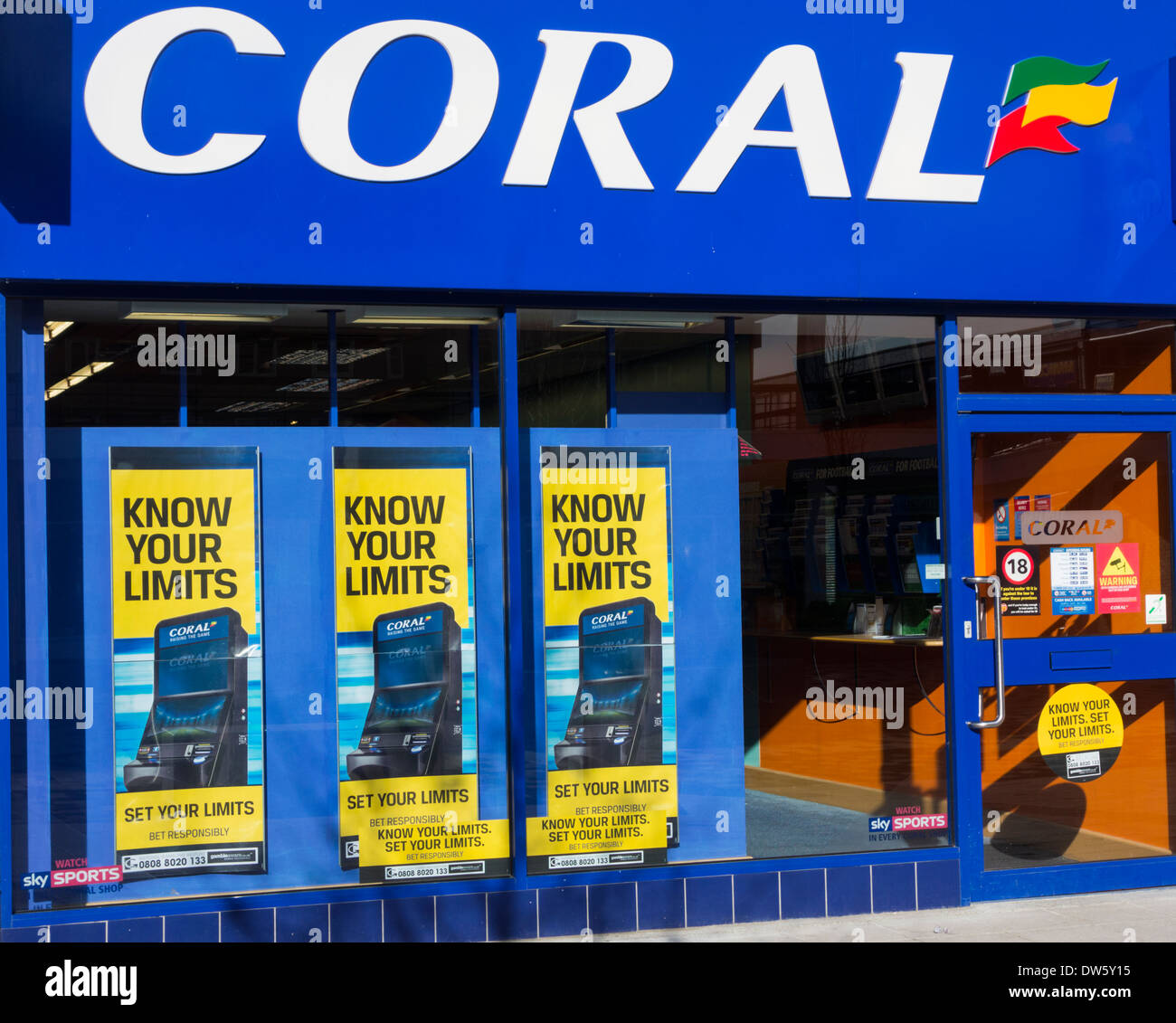 Gamble responsibly posters showing national gambling helpline number in Coral Bookmakers. - Stock Image