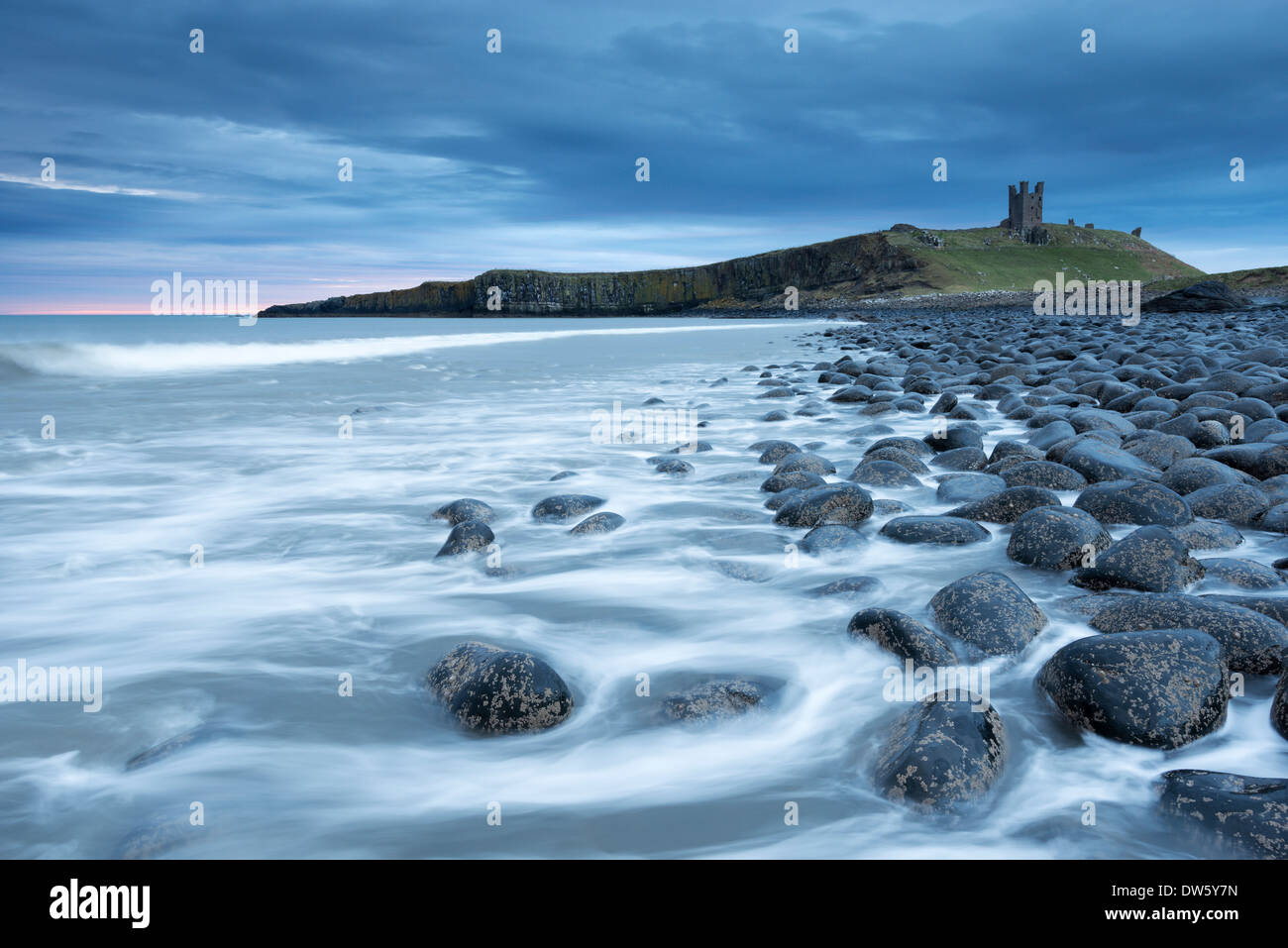 The ruins of Dunstanburgh Castle overlooking the boulder strewn shores of Embleton Bay, Northumberland, England. - Stock Image