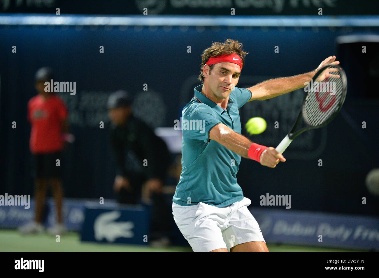 DUBAI, UAE, 27th Feb 2014. Roger Federer plays a backhand on his way to a 3-6 6-3 6-2 against Novak Djokovic in the quarterfinals of the Dubai Duty Free Tennis Championships. Federer booked his spot in the finals of the tournament with this victory Credit:  Feroz Khan/Alamy Live News - Stock Image