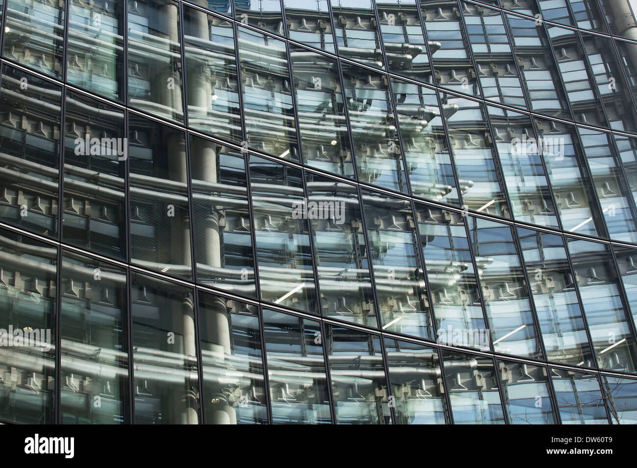 Architecture in the City of London, UK. Lloyds Building reflection as a wall of steel and glass modernism. - Stock Image