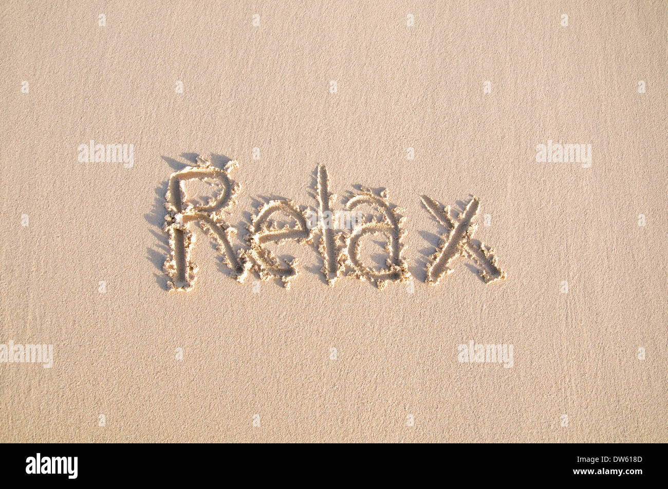 Word 'Relax' written on a sand. - Stock Image