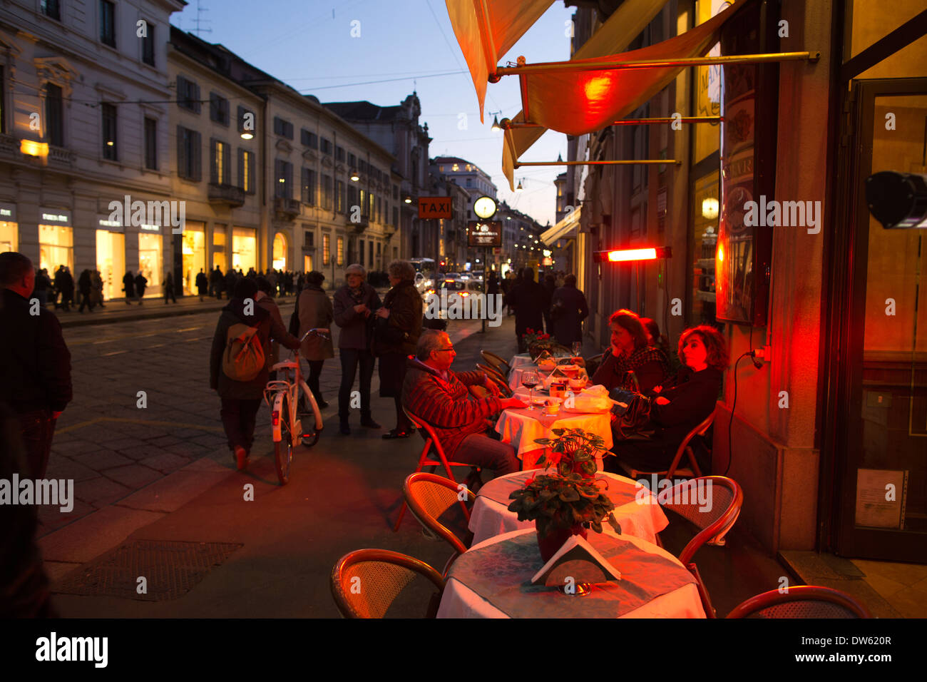 People sitting outside at a restaurant on Via Manzoni, Milan, Italy - Stock Image