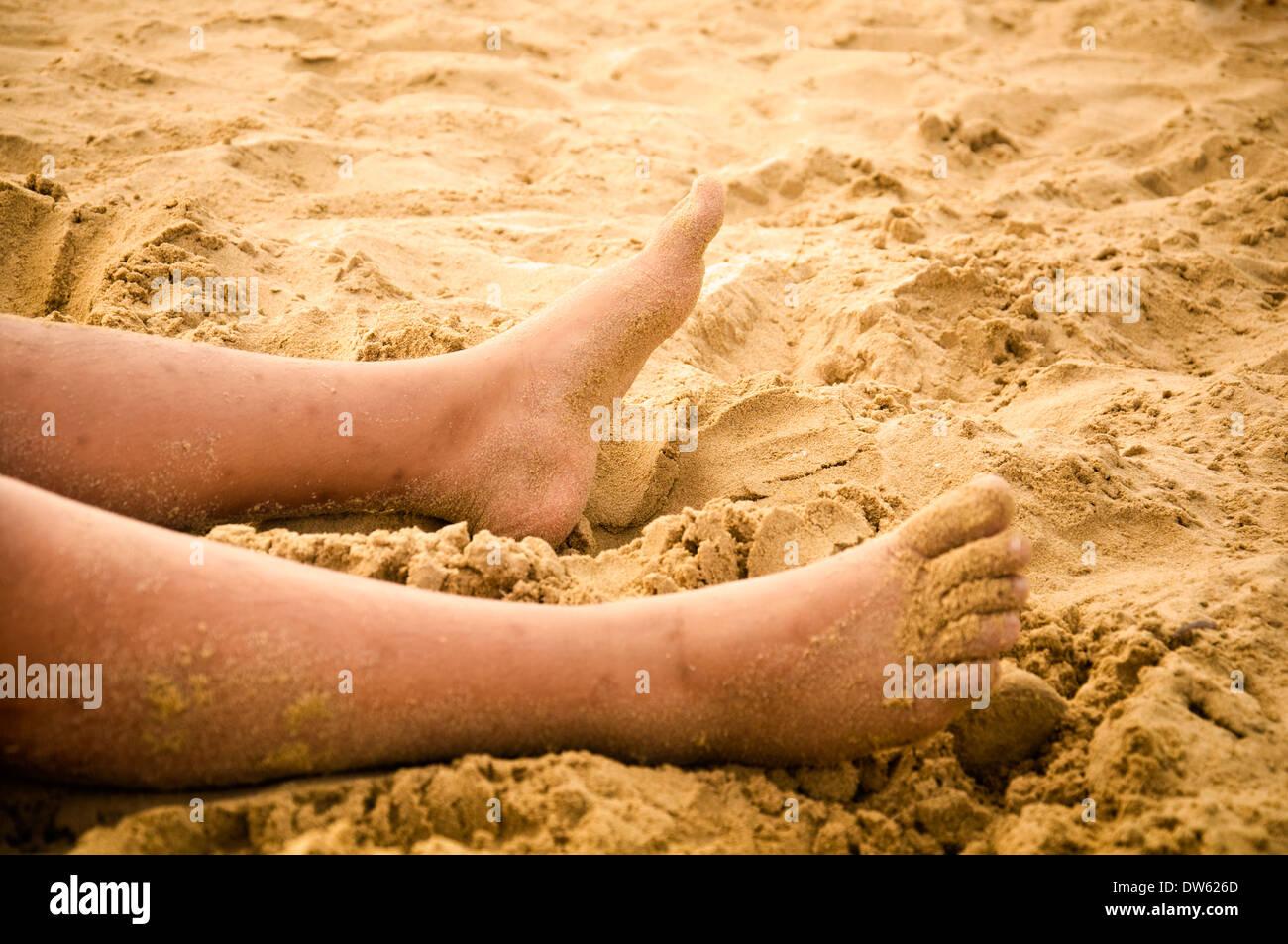 close up of feet on sandy beach - Stock Image