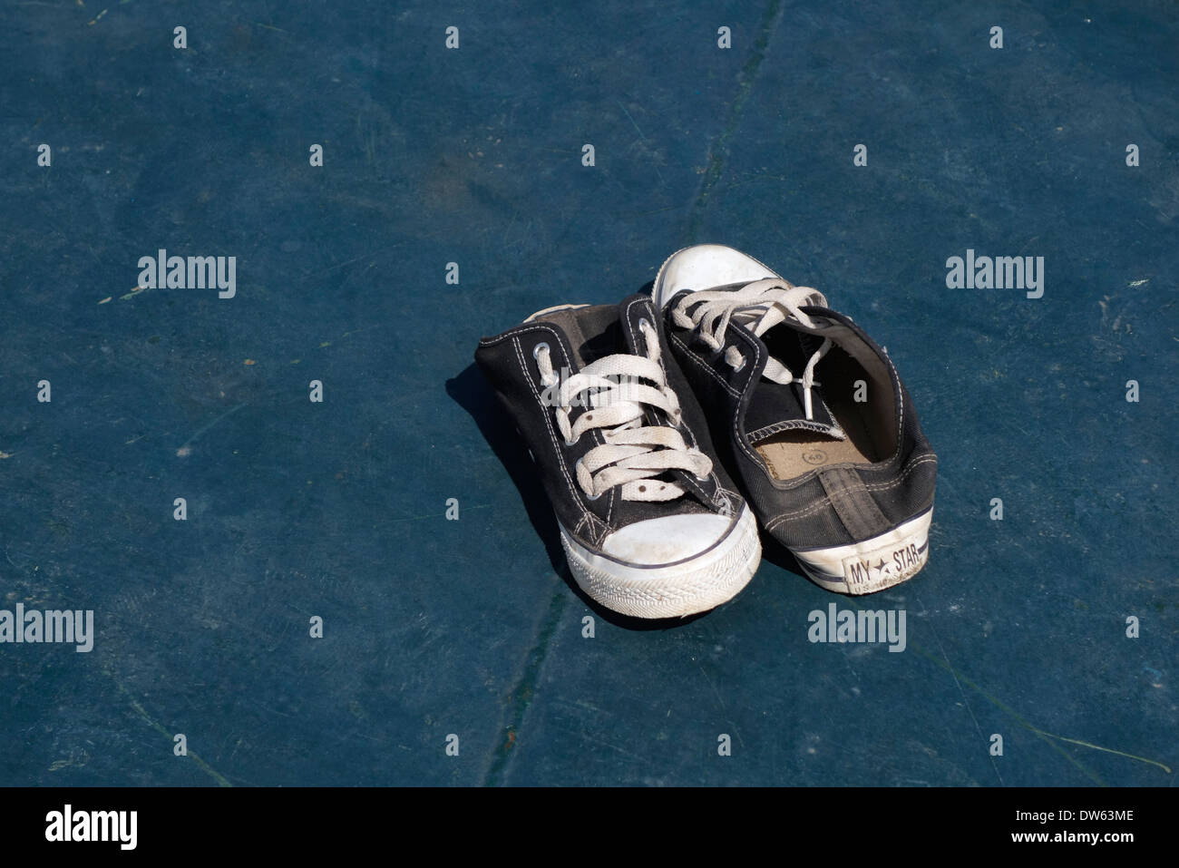A pair of sneakers with their heels folded down. - Stock Image