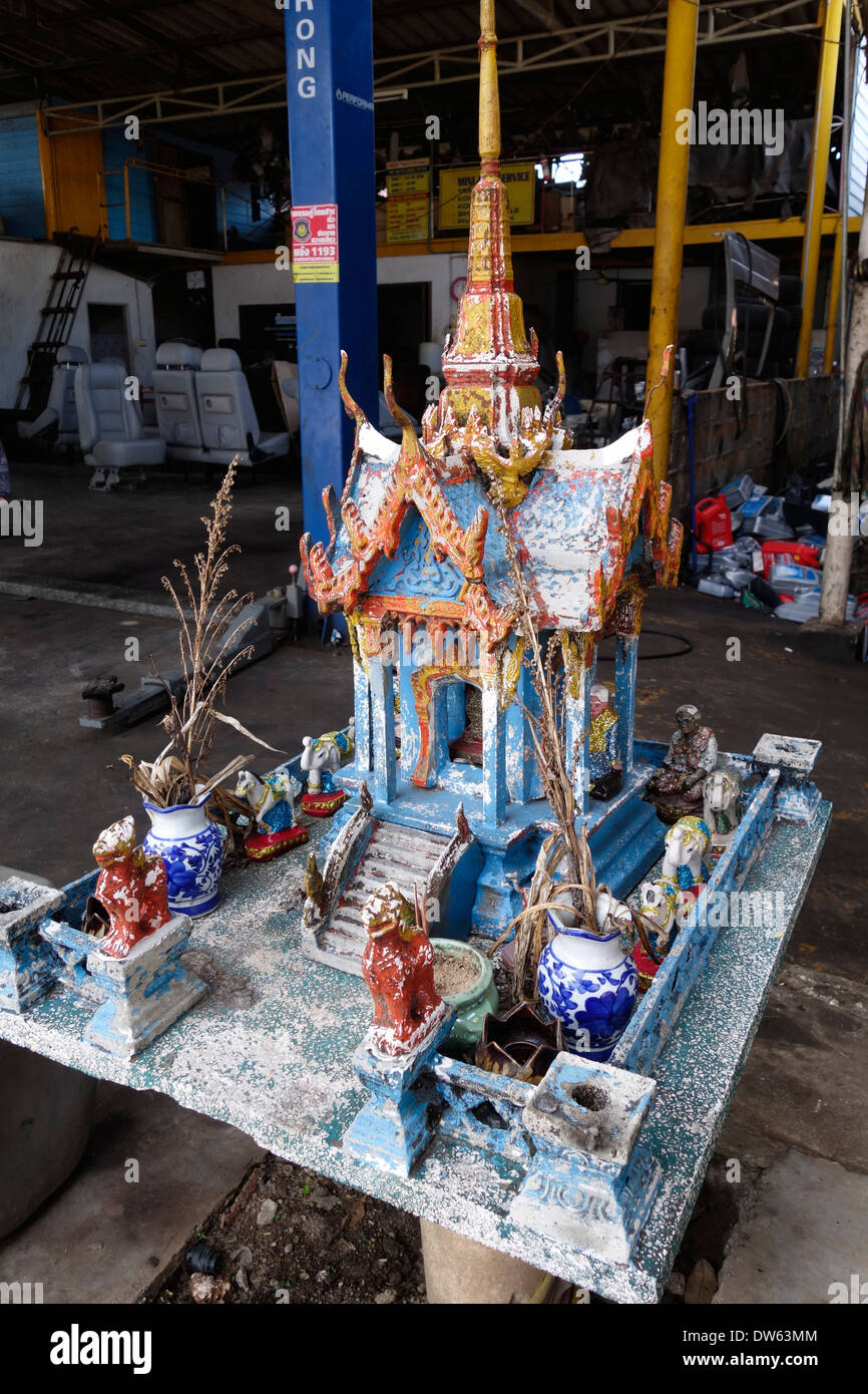 Religious shrine in an automotive shop, Trat, Thailand. - Stock Image