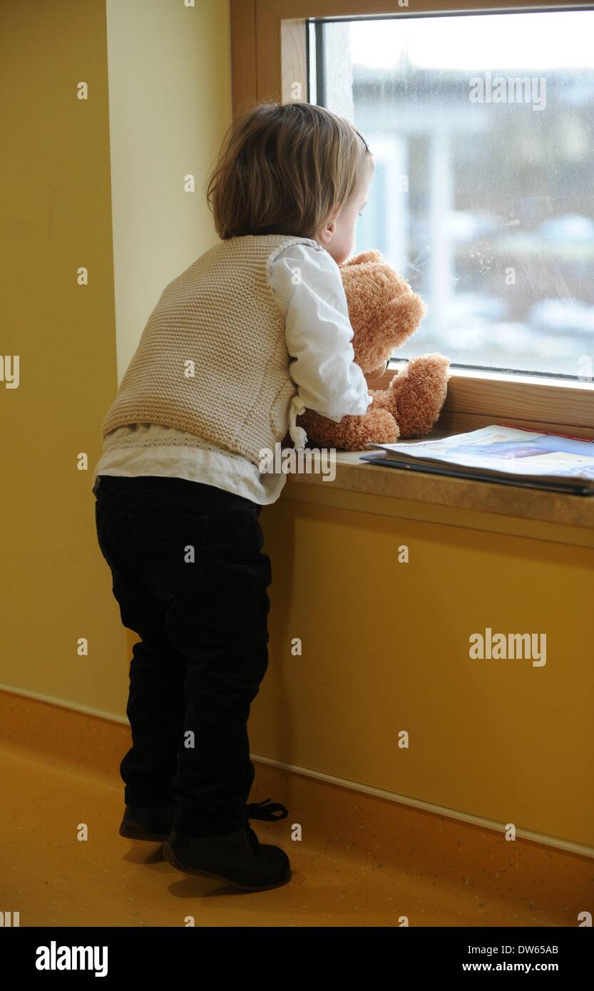 Fulda, Germany. 18th Feb, 2014. Frieda looks out of a window with a teddy bear during a visit at Fulda Hospital Stock Photo