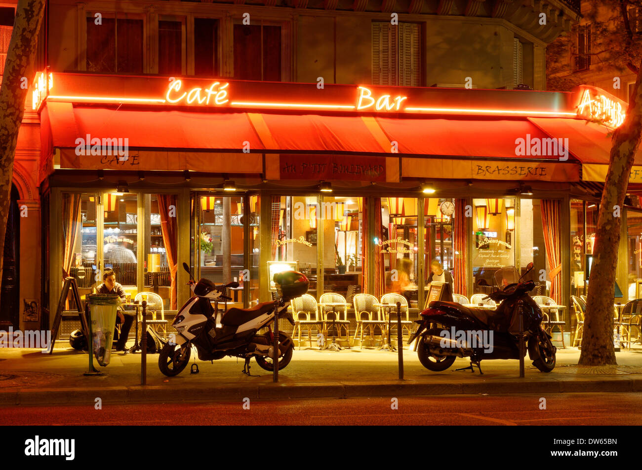 A brightly lit cafe in Paris at night - Stock Image