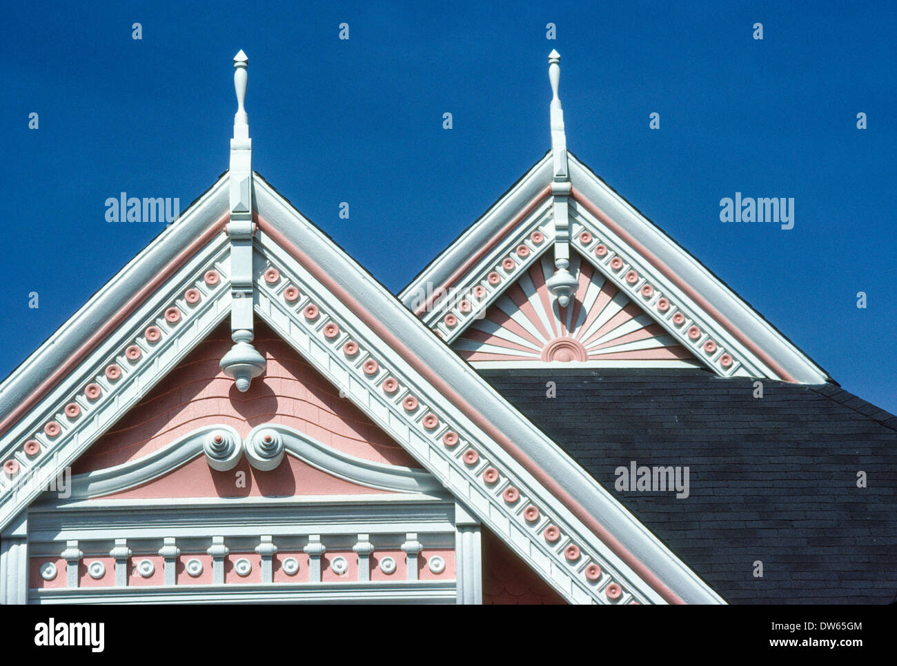painted victorian house gable peak gingerbread moulding elaborate detail - Stock Image