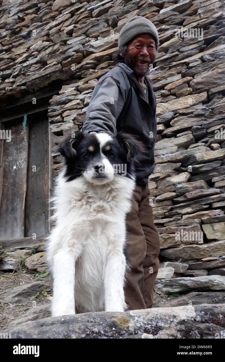 Elderly man with his dog in the village of Ngakyu Leru, Nepal - Stock Image