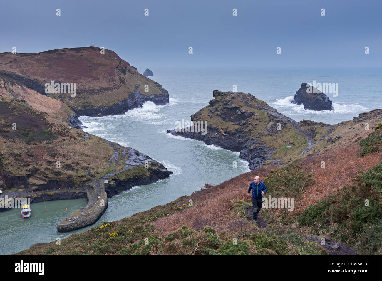 Runner on the coastal footpath at Boscastle, Cornwall, England. Winter (January) 2014. - Stock Image