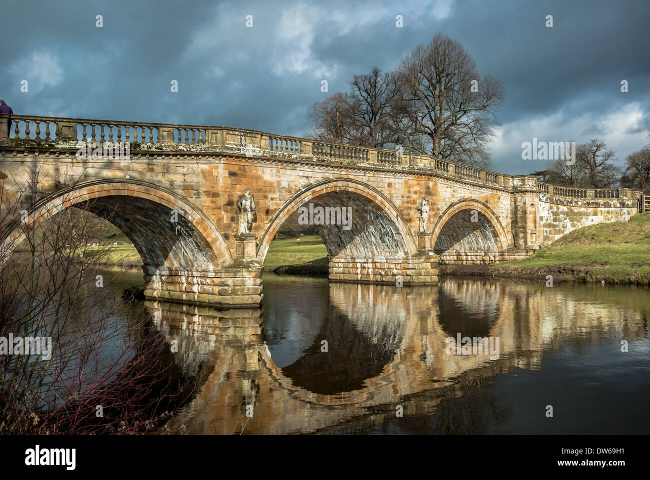 Stone road bridge over the River Derwent at Chatsworth house estate, Derbyshire. - Stock Image