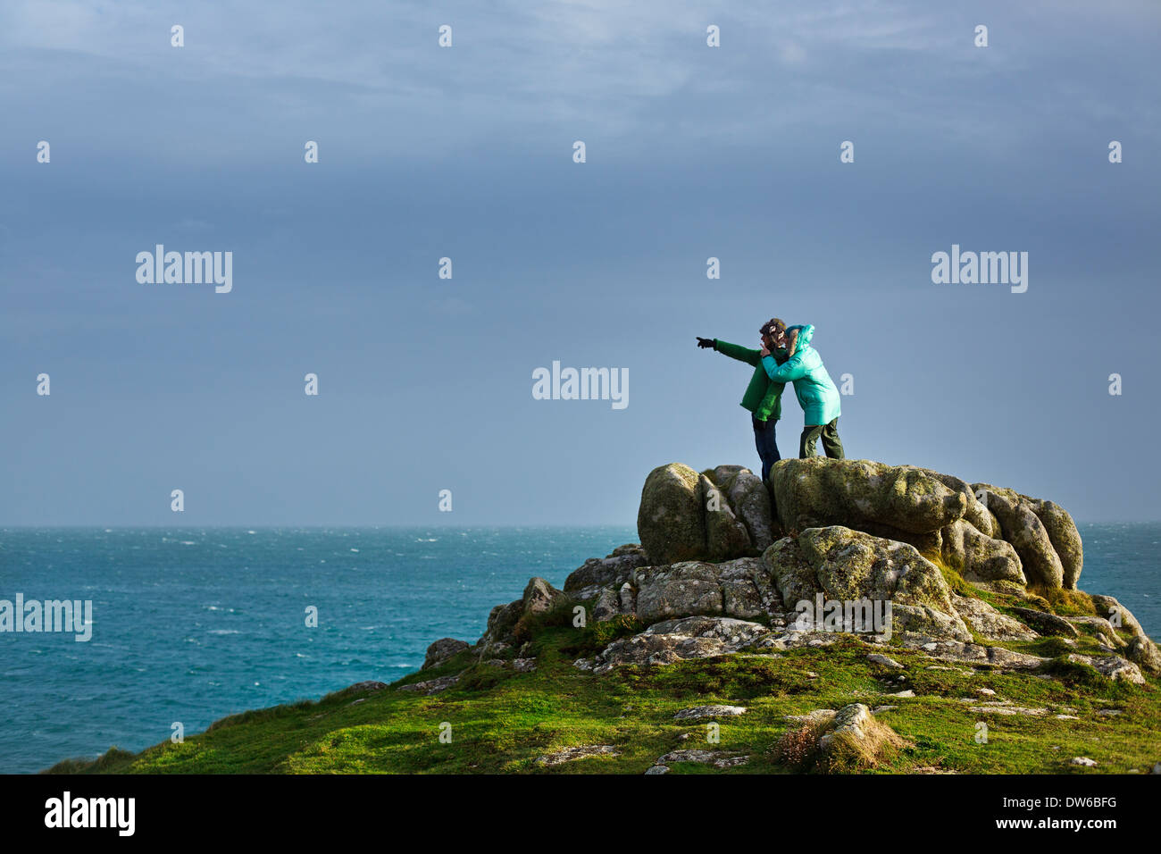 A couple standing on a rock pointing out to sea on the Isles of Scilly - Stock Image
