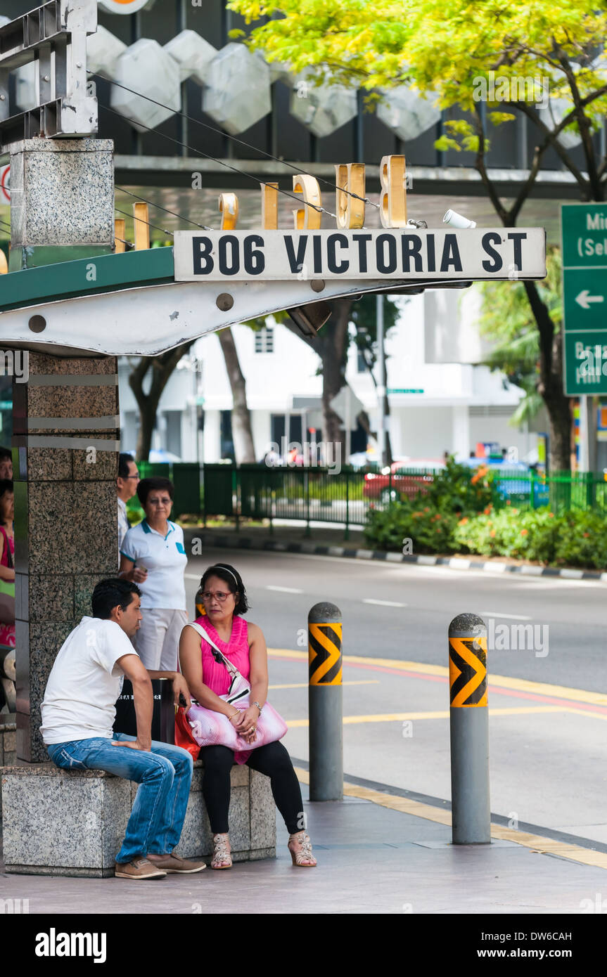 Singaporeans wait for the bus at Bugis Junction in Singapore. - Stock Image