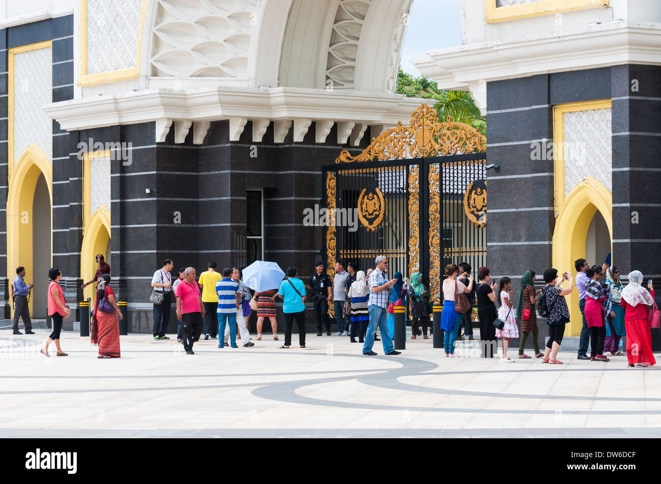 Tourists outside the massive front gate of the Istana Negara, the royal palace of Kuala Lumpur. - Stock Image