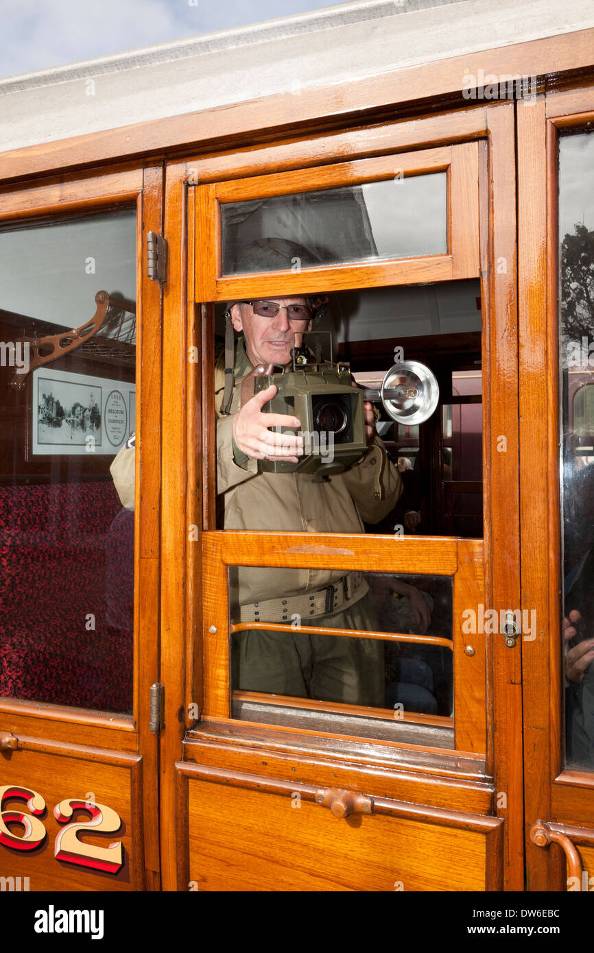 A 1940's costume weekend at Weybourne UK. A soldier takes a photograph through an open railway carriage window Stock Photo