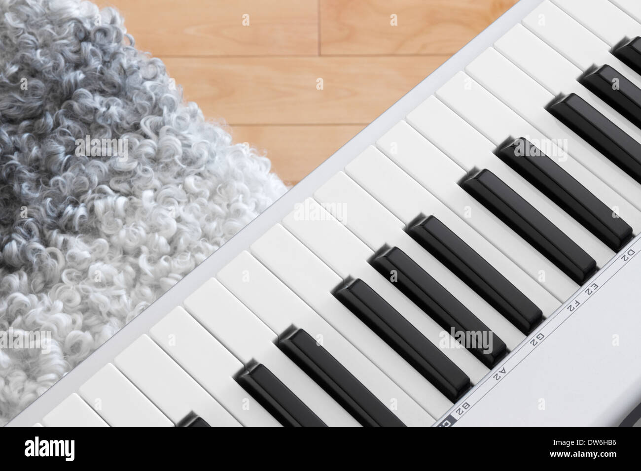 Close-up of electric piano keys and chair. - Stock Image
