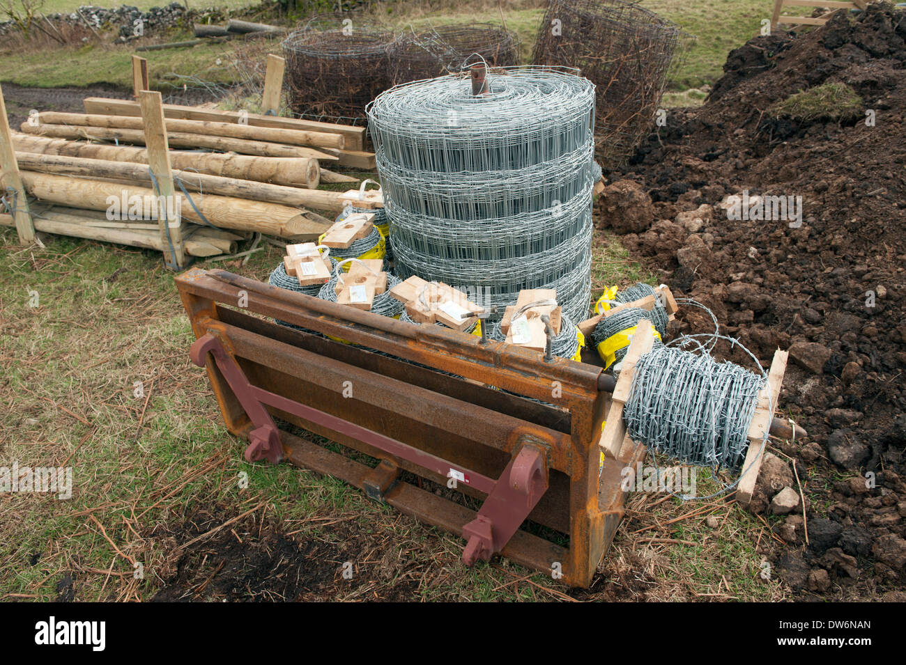 200 meter rolls of High tensile grade A barbed wire wire fencing and wooden posts on a tractor cradle attachment - Stock Image