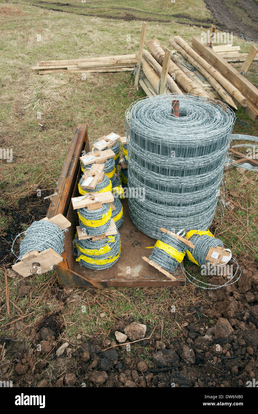 200 metre rolls of High tensile grade A barbed wire wire fencing and wooden posts on a tractor cradle attachment - Stock Image
