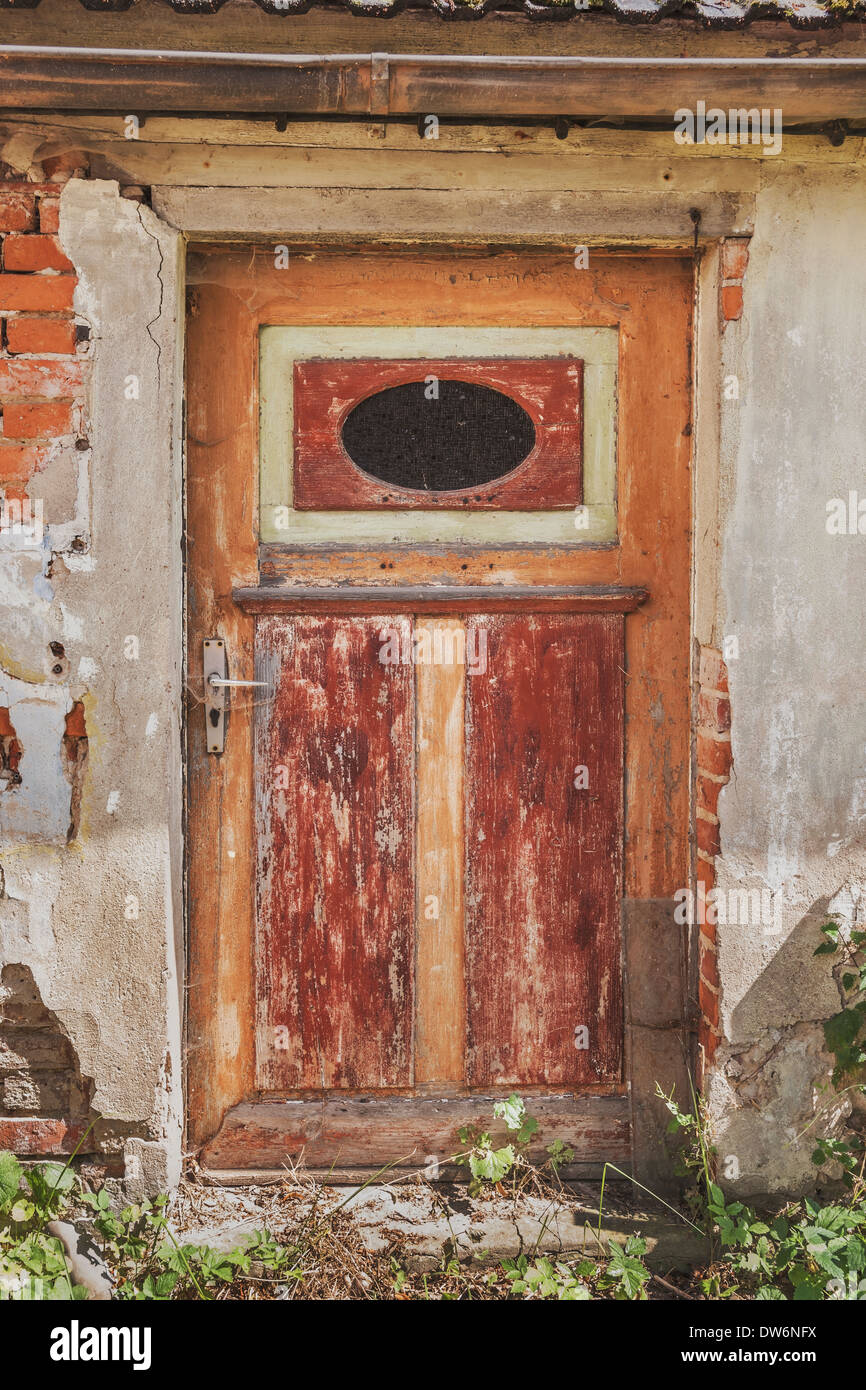 Old door in a dilapidated apartment building. - Stock Image
