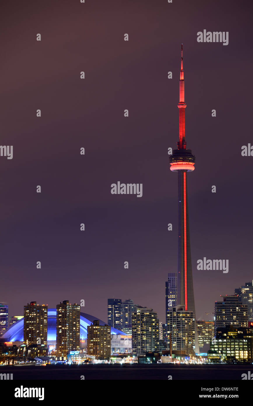 Toronto CN tower with red lights and Rogers Centre Skydome at night in winter - Stock Image