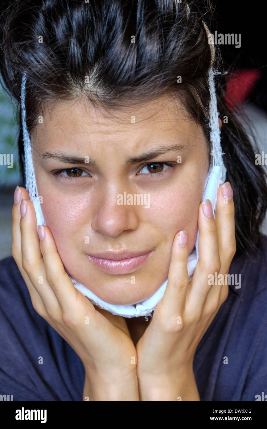 Young girl with ice pack recovering from extraction of wisdom teeth - Stock Image