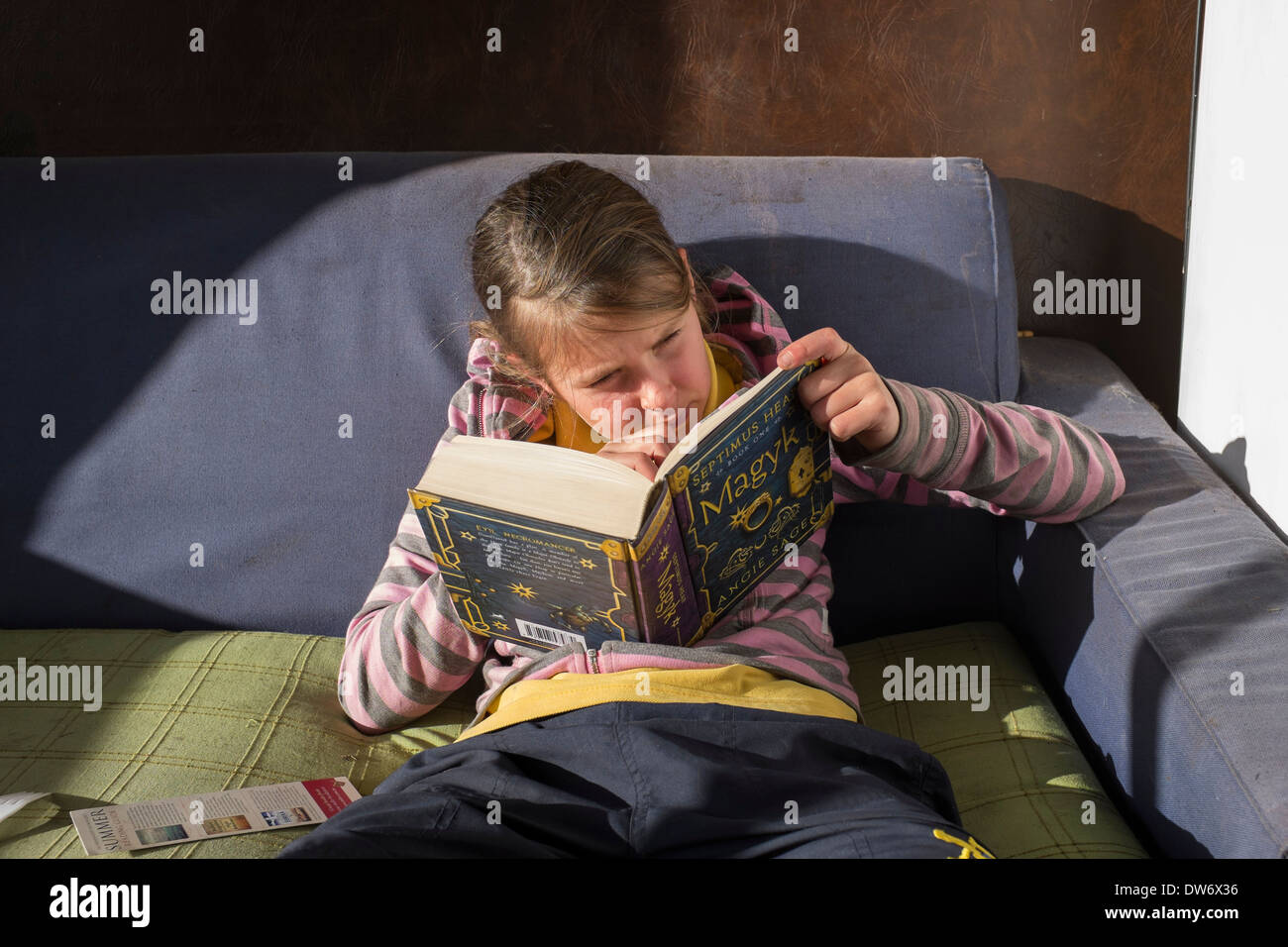 A child engrossed in reading a book on a couch - Stock Image