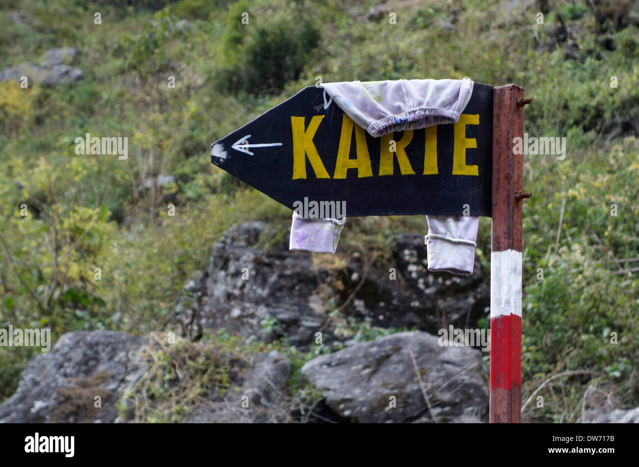 Childs clothing drying on a sign to the village of Karte, Nepal. - Stock Image