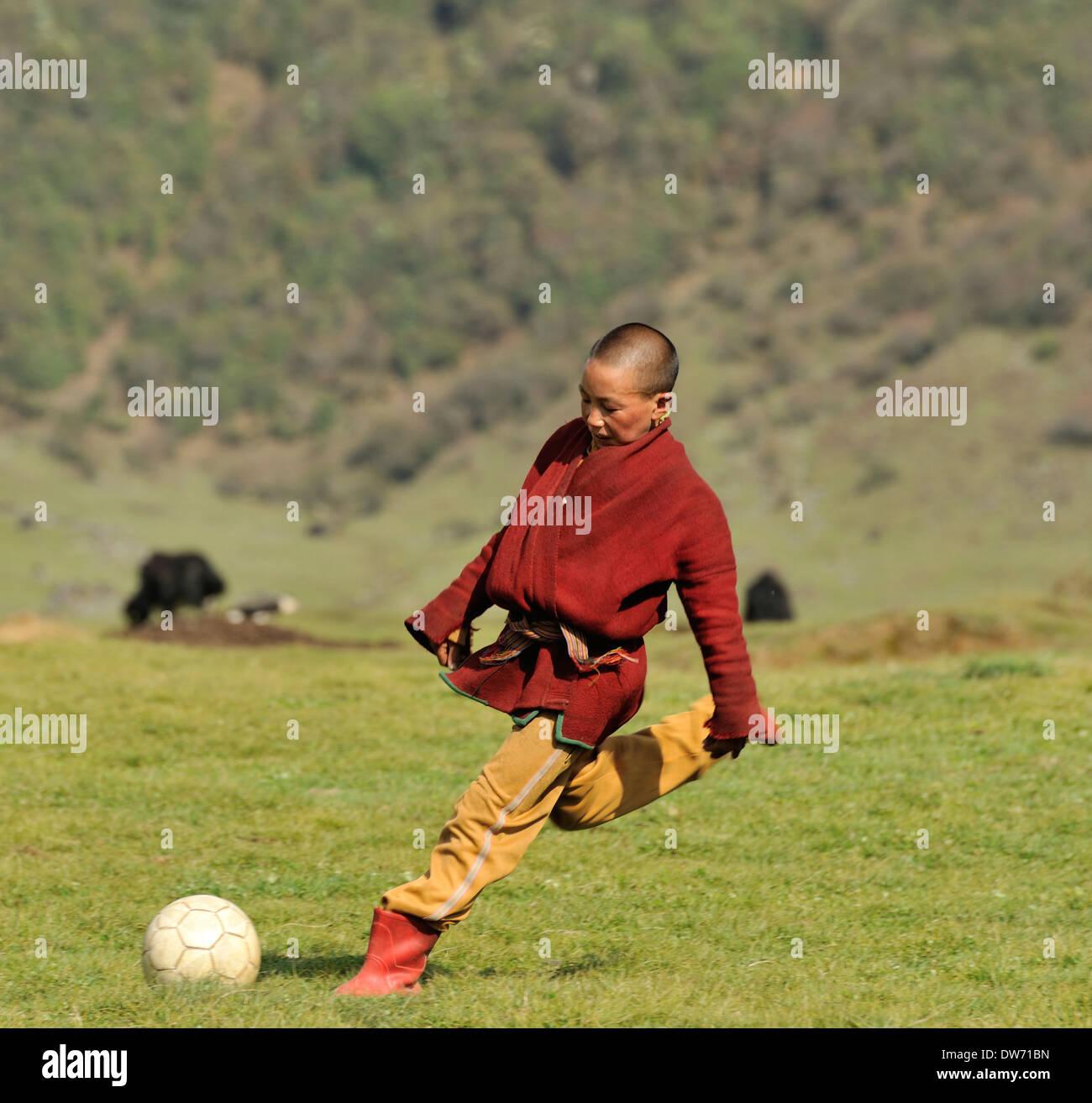 Boys wearing traditional clothes play football in school playground, village of Sakteng on Merak Sakteng trek, Eastern Stock Photo