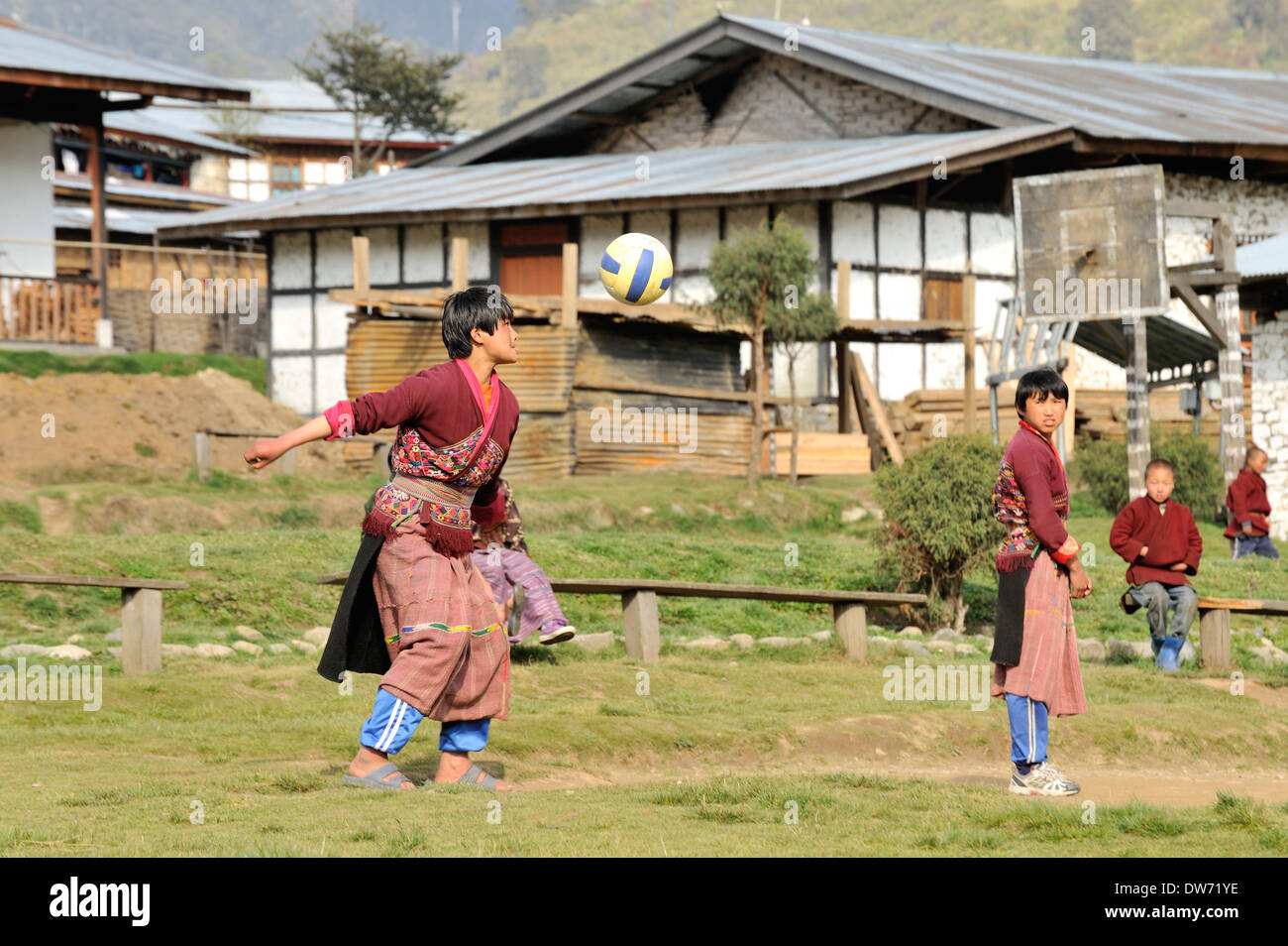 Schoolchildren wearing traditional clothes play volleyball in school playground, village of Sakteng, Eastern Bhutan - Stock Image