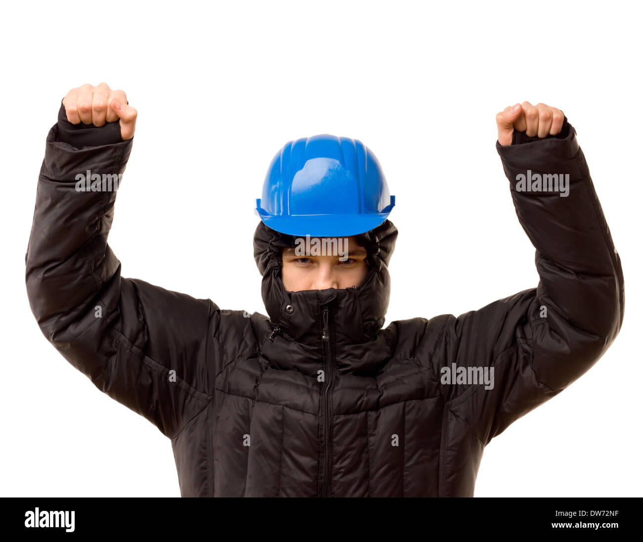 Belligerent young thug raising his arms in a threatening gesture as he stands glaring malevolently in a black balaclava and hardhat, on white. - Stock Image