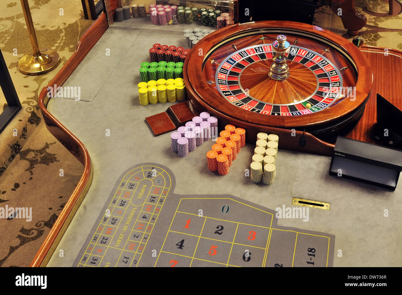 image with a casino roulette wheel with the ball on number zero - Stock Image