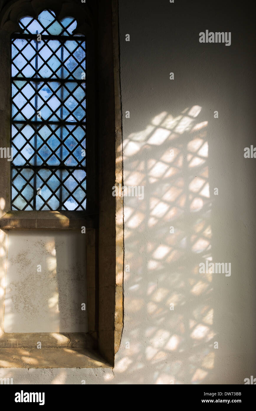 Diamond leaded windows in a church with sunlight and shadows. UK - Stock Image